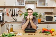 Красивый кавказский молодой человек, сидя на таблице Здоровый уклад жизни casserole варя вкусный домашний домодельный рецепт еда  стоковое фото
