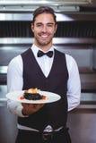 Красивый кельнер держа плиту спагетти чернил кальмара Стоковые Фото