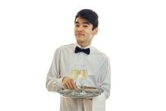 Красивый кельнер усмехаясь в белой рубашке смотрит прямым и держащ поднос с 2 стеклами вина Стоковая Фотография RF