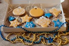 Красивый комплект рождества различных печений пряника праздника в присутствующей коробке и желтом цвете, голубых шариках Стоковое Фото