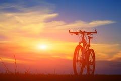 Красивый конец вверх по сцене велосипеда на заходе солнца, Стоковые Фото