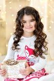 Красивый конец вверх по portraite курчавой девушки с светами гирлянд рождества золота волшебными и подарочной коробкой украшений  Стоковые Изображения