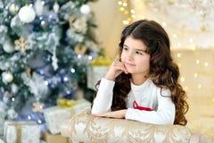 Красивый конец вверх по portraite курчавой девушки с светами гирлянд рождества золота волшебными и подарочной коробкой украшений  Стоковые Фото