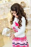 Красивый конец вверх по portraite курчавой девушки с светами гирлянд рождества золота волшебными и подарочной коробкой украшений  Стоковая Фотография