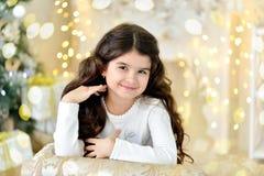 Красивый конец вверх по portraite курчавой девушки с светами гирлянд рождества золота волшебными и подарочной коробкой украшений  Стоковое Изображение RF
