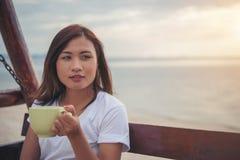 Красивый кофе питья женщины пока сидящ на качании на пляже Стоковое Изображение