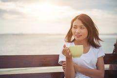 Красивый кофе питья женщины пока сидящ на качании на пляже Стоковое Фото