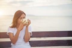 Красивый кофе питья женщины пока сидящ на качании на пляже Стоковое фото RF