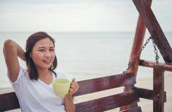 Красивый кофе питья женщины пока сидящ на качании на пляже Стоковая Фотография RF