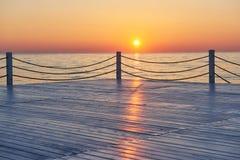 Красивый красочный заход солнца над морем и солнцем светит померанцовое небо Стоковые Изображения