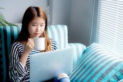 Красивый кредитной карточки пользы усаживания женщины портрета молодой азиатской с компьтер-книжкой и кофе питья Стоковые Изображения