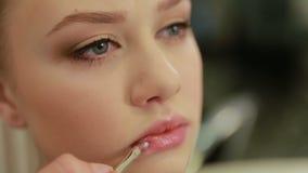 Красивый крупный план губ девушки, визажист прикладывает щетку для состава, полные губы губной помады, женщину в салоне красоты Д сток-видео