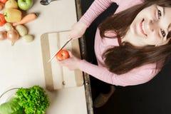 Красивый кусок женщины, режущ томат в кухне, варя, подготавливает vegetable салат, смотря улыбку камеры счастливую Стоковое Изображение RF