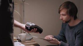 Красивый клиент человека оплачивая кредитной карточкой безконтактной в современном кафе акции видеоматериалы