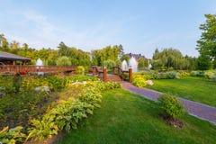 Красивый ландшафт зеленой природы в парке с flowerbeds живописных фонтанов лужаек с чистой водой против стоковое изображение rf