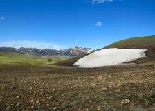 Красивый ландшафт зеленых гор долины и риолита Hvanngil покрытых со снегом, следом Laugavegur, гористой местностью Исландии стоковые фотографии rf