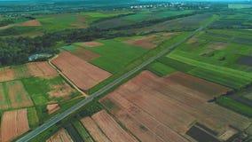 Красивый ландшафт и деревня воздушные с голубыми небом и облаками, дорогой, сельскохозяйственными угодьями и красочными полями 4K