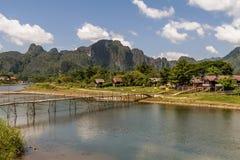 Красивый ландшафт с бамбуковым мостом на реке песни Nam в Vang Vieng, Лаосе стоковые фотографии rf