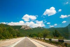 Красивый ландшафт с дорогой в горной области, небе и вычисляемых облаках Стоковая Фотография