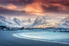 Красивый ледовитый песчаный пляж, море и снежные горы на заходе солнца Стоковое фото RF