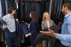 Красивый магазин моды бизнесмена и женщины, клиенты выбирая одежды в магазине розничной торговли Стоковое фото RF