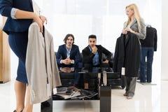 Красивый магазин моды бизнесмена и женщины, клиенты выбирая одежды в магазине розничной торговли Стоковые Фотографии RF