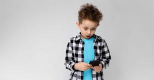 Красивый мальчик в рубашке шотландки, голубой рубашке и джинсах стоит на серой предпосылке Мальчик держит телефон Стоковое Фото