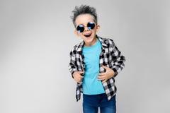 Красивый мальчик в рубашке шотландки, голубой рубашке и джинсах стоит на серой предпосылке Мальчик носит вокруг стекел _ Стоковая Фотография RF