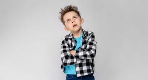 Красивый мальчик в рубашке шотландки, голубой рубашке и джинсах стоит на серой предпосылке Мальчик сложил его оружия над его Стоковое фото RF