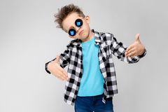 Красивый мальчик в рубашке шотландки, голубой рубашке и джинсах стоит на серой предпосылке Мальчик носит вокруг стекел Красный Стоковая Фотография RF