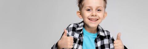 Красивый мальчик в рубашке шотландки, голубой рубашке и джинсах стоит на серой предпосылке Улыбки мальчика и класс выставок стоковые фотографии rf
