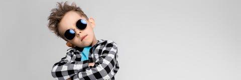 Красивый мальчик в рубашке шотландки, голубой рубашке и джинсах стоит на серой предпосылке Мальчик носит вокруг стекел Красный стоковое изображение rf