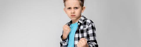 Красивый мальчик в рубашке шотландки, голубой рубашке и джинсах стоит на серой предпосылке Мальчик стоит в представлении боксера стоковое изображение