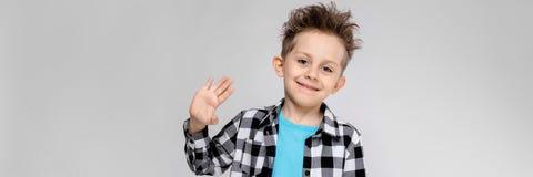 Красивый мальчик в рубашке шотландки, голубой рубашке и джинсах стоит на серой предпосылке Улыбки и выставки мальчика ладонь стоковые изображения rf