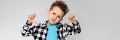 Красивый мальчик в рубашке шотландки, голубой рубашке и джинсах стоит на серой предпосылке Мальчик сложил его оружия над его стоковые изображения