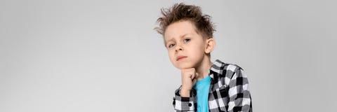 Красивый мальчик в рубашке шотландки, голубой рубашке и джинсах стоит на серой предпосылке Мальчик поддерживает его подбородок с  стоковые изображения rf
