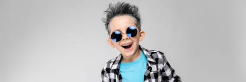 Красивый мальчик в рубашке шотландки, голубой рубашке и джинсах стоит на серой предпосылке Мальчик носит вокруг стекел _ стоковые фотографии rf