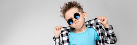 Красивый мальчик в рубашке шотландки, голубой рубашке и джинсах стоит на серой предпосылке Мальчик носит вокруг стекел стоковая фотография rf