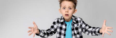 Красивый мальчик в рубашке шотландки, голубой рубашке и джинсах стоит на серой предпосылке Мальчик распространил его руки в обоих стоковое изображение rf