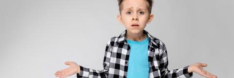 Красивый мальчик в рубашке шотландки, голубой рубашке и джинсах стоит на серой предпосылке Мальчик распространил его руки в обоих стоковая фотография rf