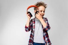 Красивый мальчик в рубашке шотландки, серой рубашке и джинсах стоит на серой предпосылке Мальчик в красных наушниках Мальчик прин Стоковые Фото