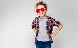 Красивый мальчик в рубашке шотландки, серой рубашке и джинсах стоит на серой предпосылке Мальчик в красных солнечных очках Положе Стоковая Фотография RF