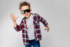 Красивый мальчик в рубашке шотландки, серой рубашке и джинсах стоит на серой предпосылке Мальчик в черных солнечных очках Мальчик Стоковая Фотография RF