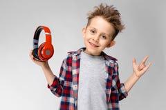 Красивый мальчик в рубашке шотландки, серой рубашке и джинсах стоит на серой предпосылке Мальчик в красных наушниках Мальчик прин Стоковое Изображение