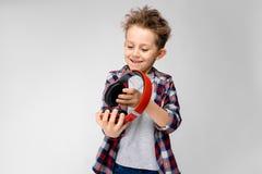 Красивый мальчик в рубашке шотландки, серой рубашке и джинсах стоит на серой предпосылке Мальчик в красных наушниках Мальчик прин Стоковое Фото