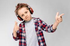 Красивый мальчик в рубашке шотландки, серой рубашке и джинсах стоит на серой предпосылке Мальчик в красных наушниках Мальчик маль Стоковые Фото