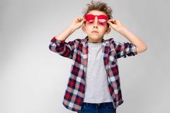 Красивый мальчик в рубашке шотландки, серой рубашке и джинсах стоит на серой предпосылке Мальчик в красных солнечных очках Мальчи Стоковые Фото