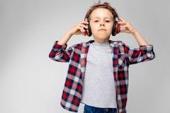 Красивый мальчик в рубашке шотландки, серой рубашке и джинсах стоит на серой предпосылке Мальчик в красных наушниках Мальчик Стоковые Изображения RF