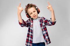 Красивый мальчик в рубашке шотландки, серой рубашке и джинсах стоит на серой предпосылке Мальчик в красных наушниках показывает a Стоковые Изображения RF