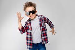 Красивый мальчик в рубашке шотландки, серой рубашке и джинсах стоит на серой предпосылке Мальчик в черных солнечных очках Мальчик Стоковое Изображение